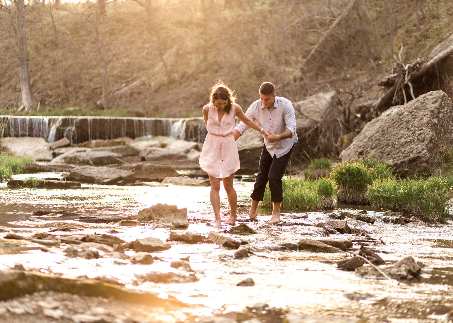 two holding hands walking across rocks through the creek