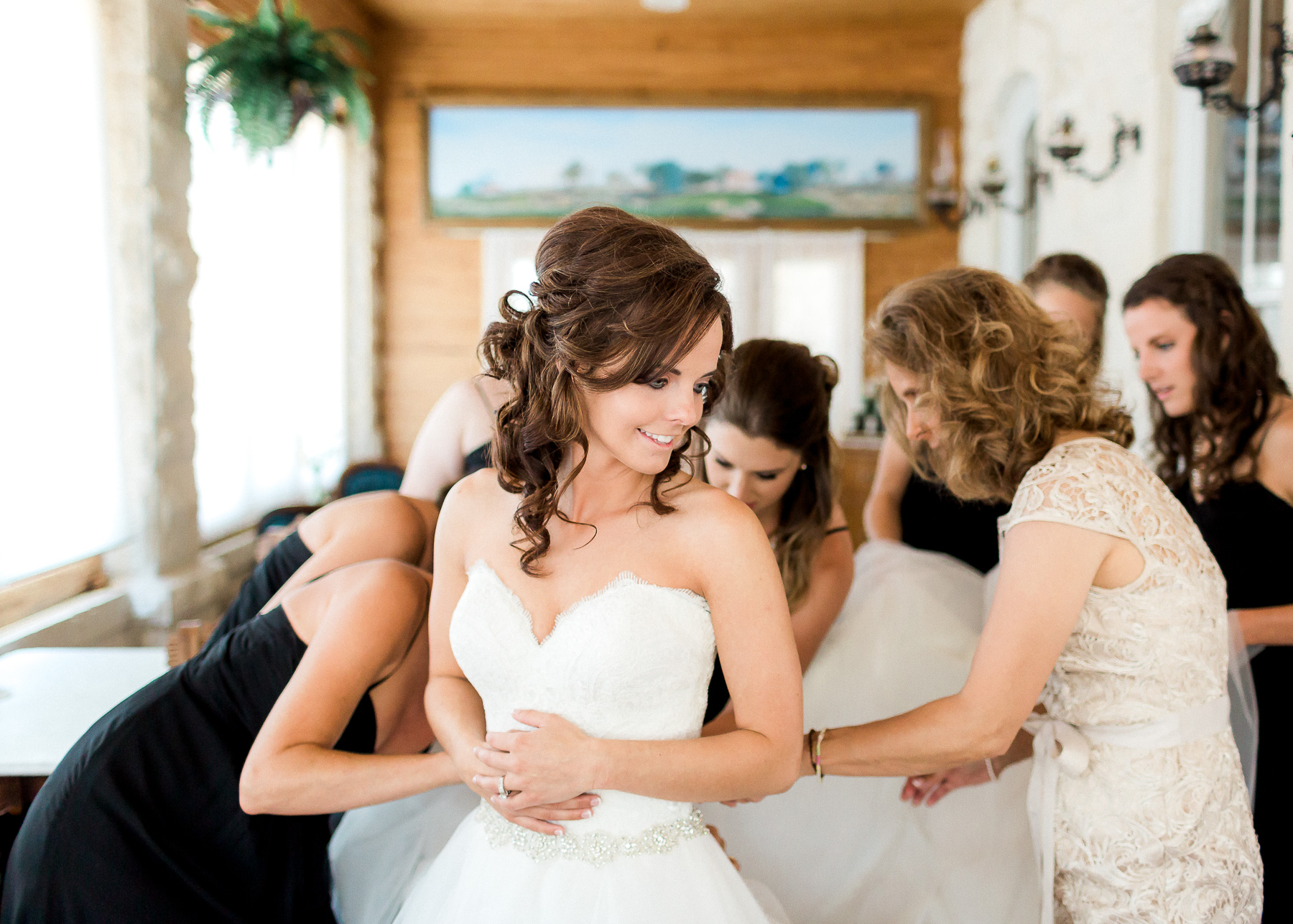 mother and sister helping button her wedding dress