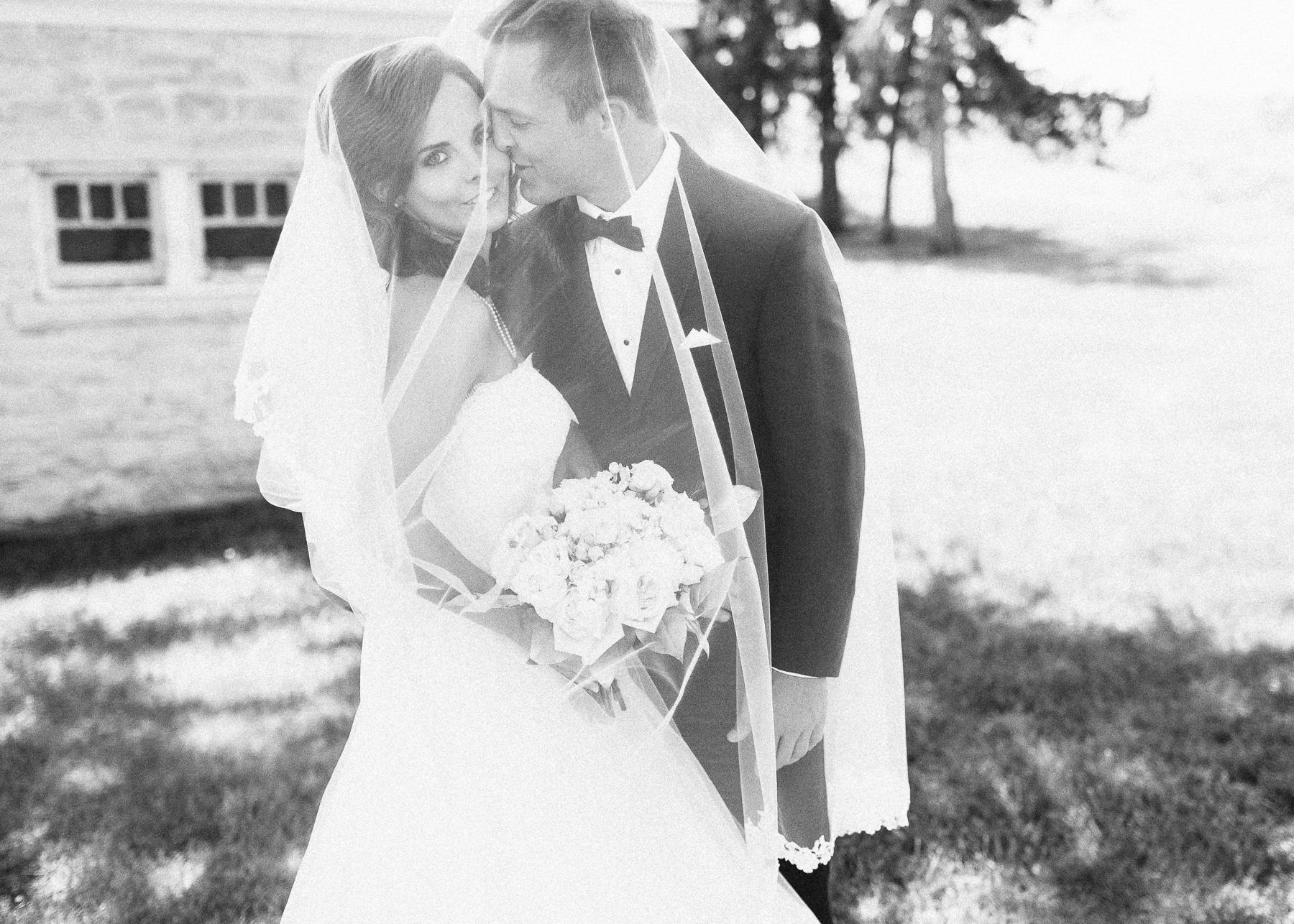 bride and groom underneath veil