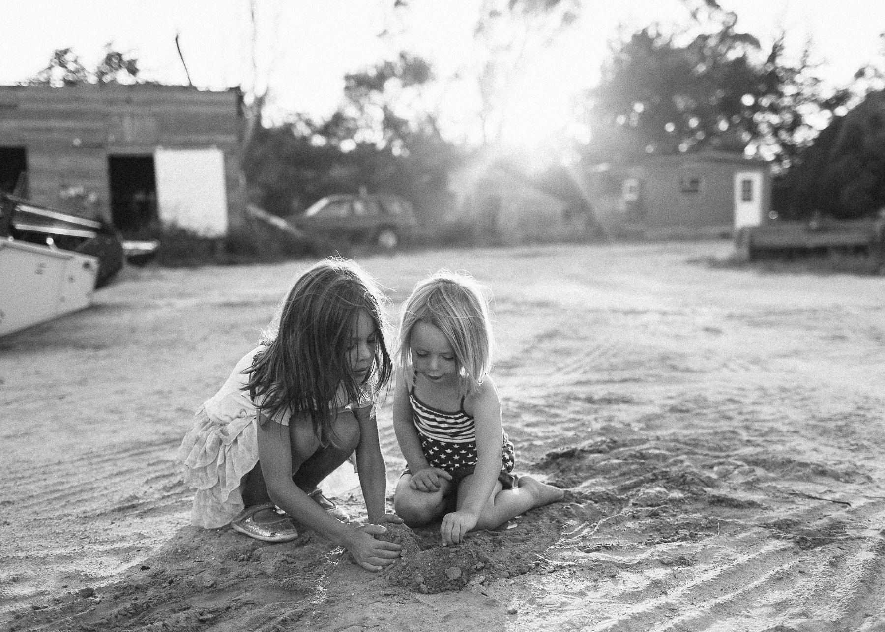 girls digging in dirt together at sunset