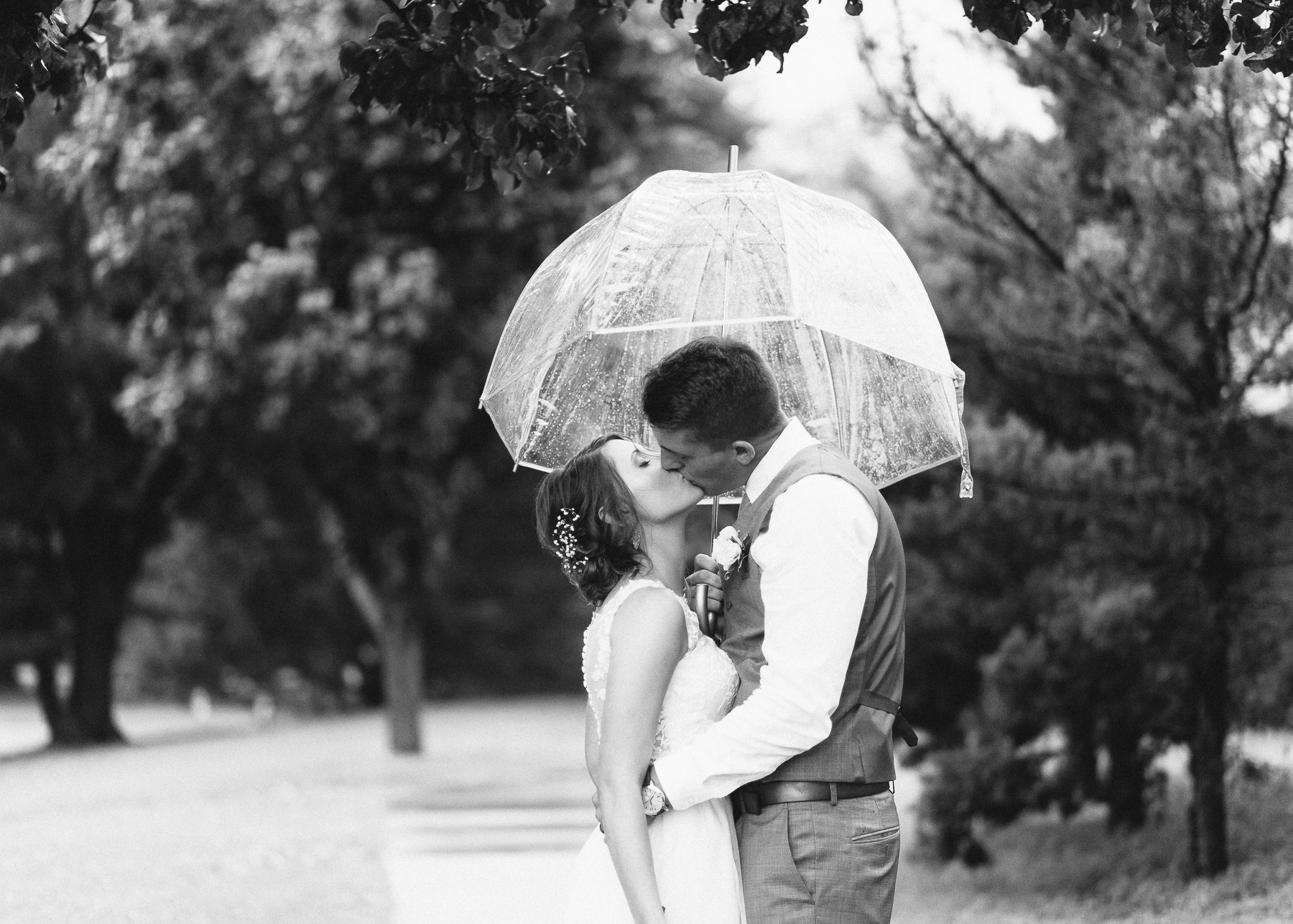 Zach and Abby kissing under umbrella