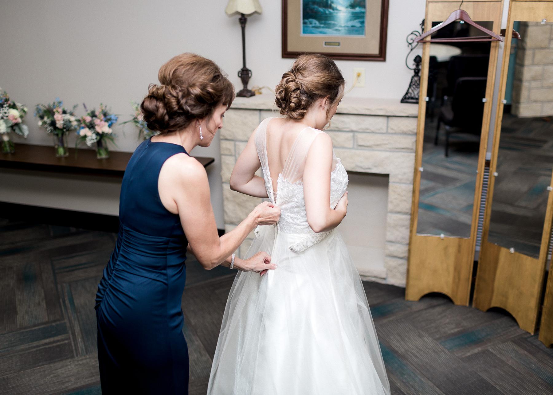 mother of bride zipping on wedding dress