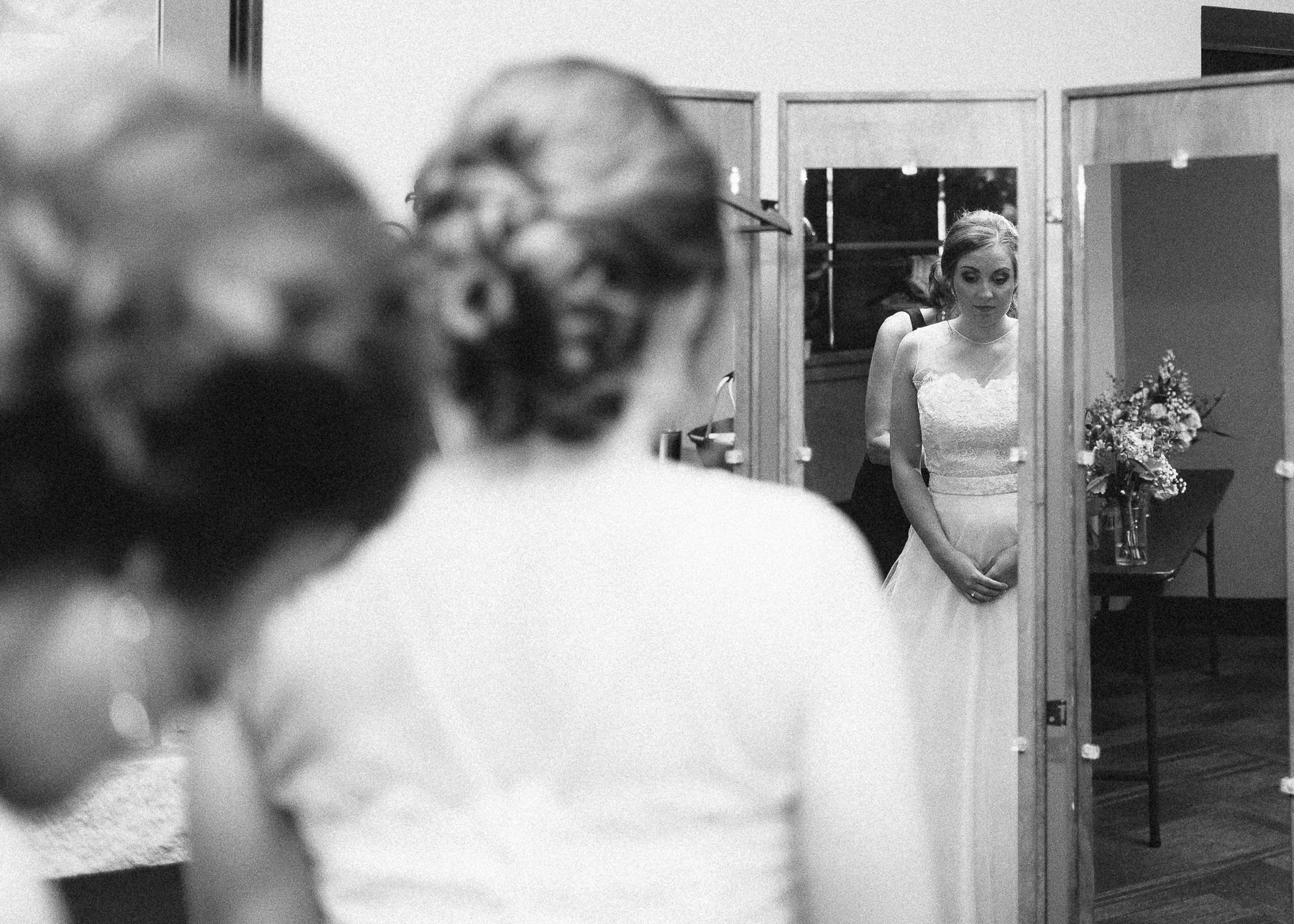 bride looking at wedding dress in the mirror