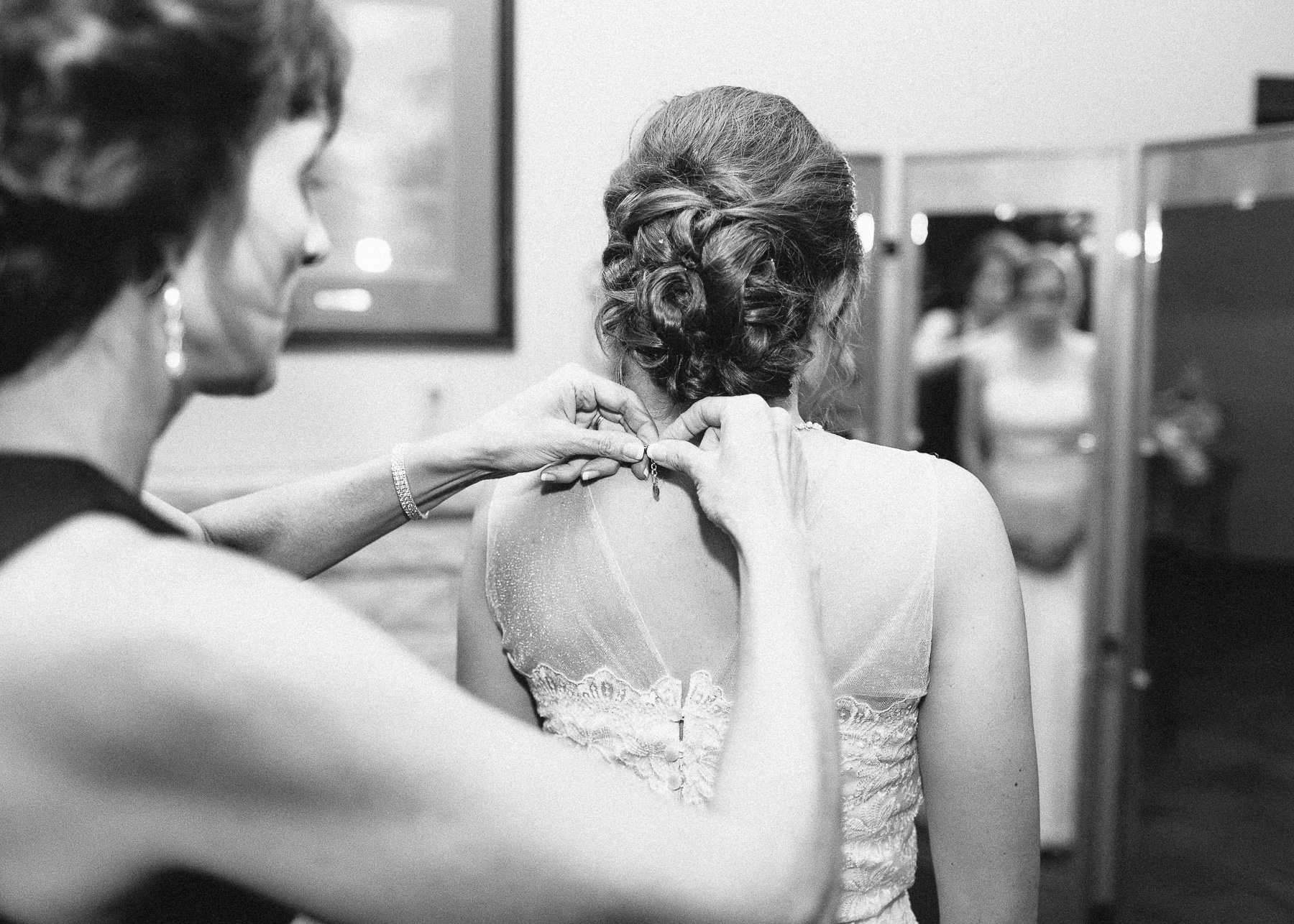 mother of bride putting on necklace