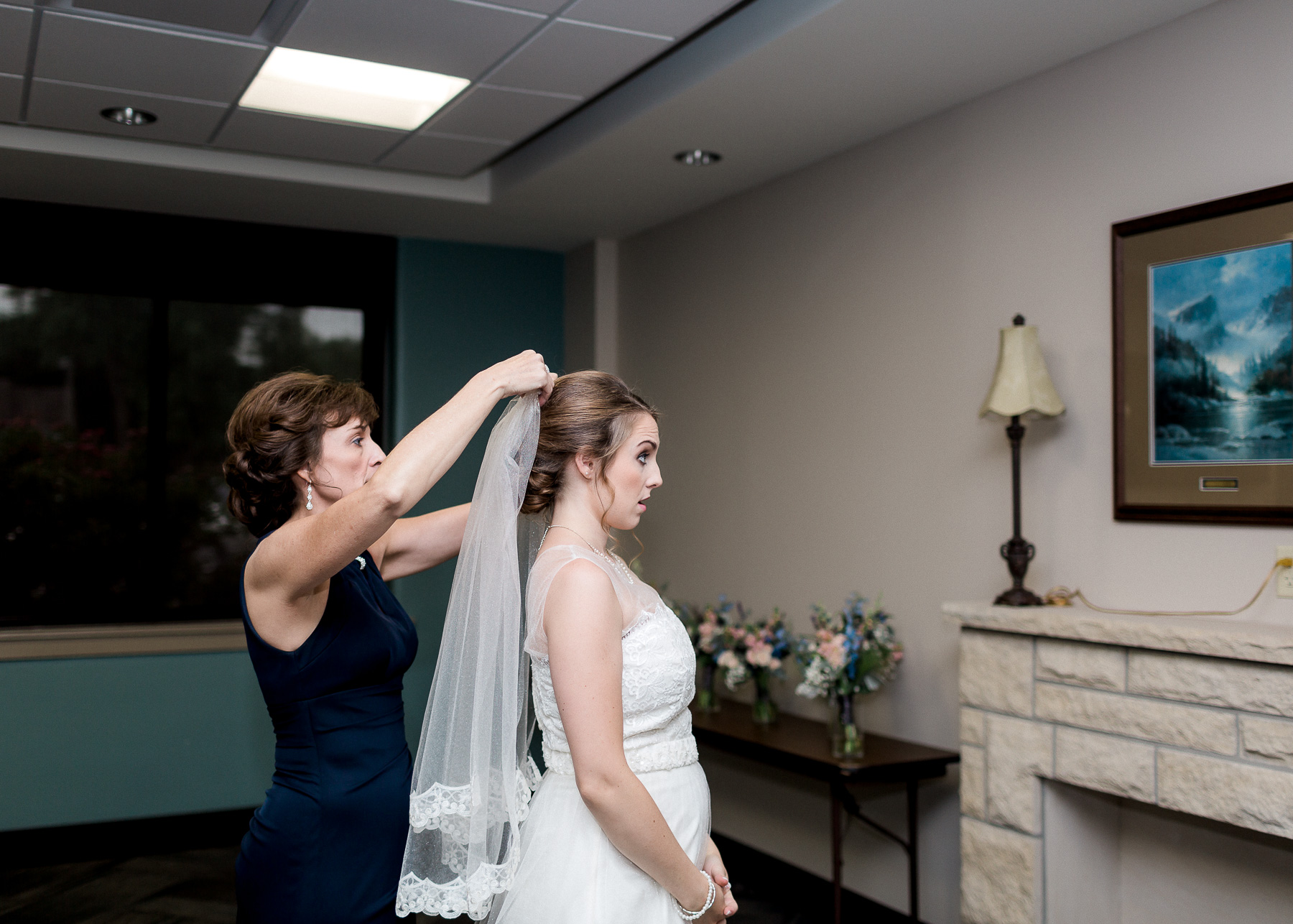 mother putting veil on bride