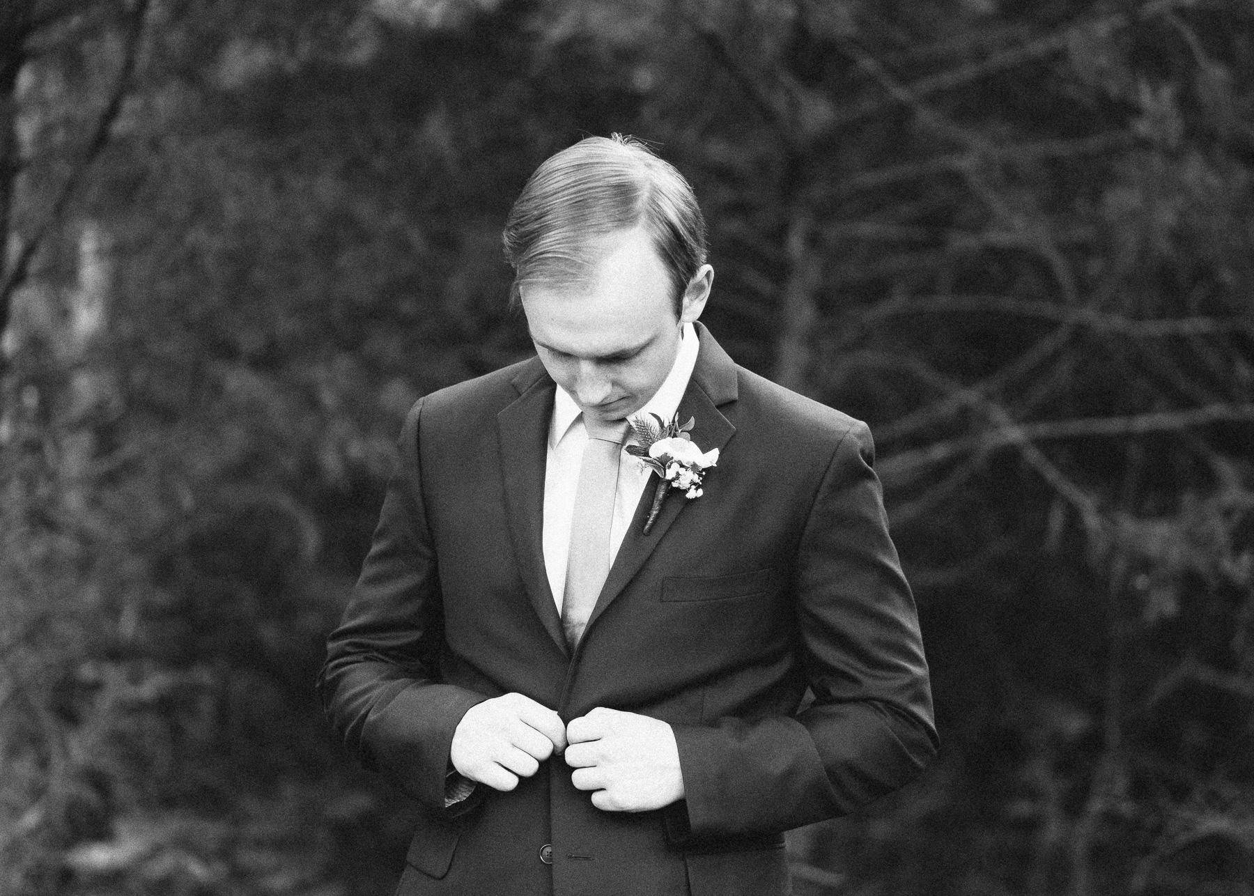 groom buttoning coat