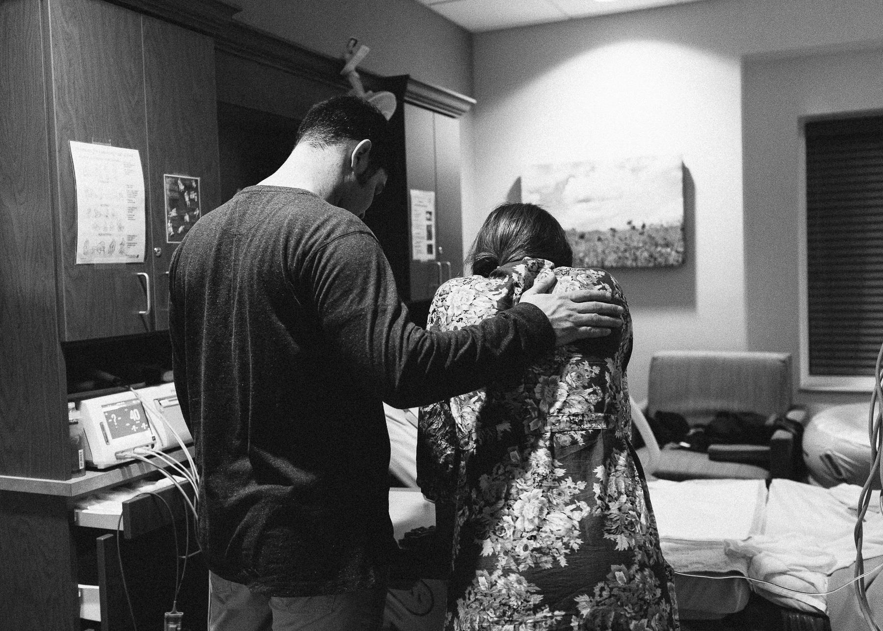 husband praying over birthing momma