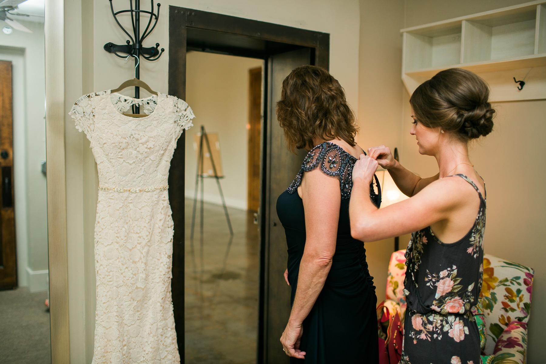 Bride pinning mom's dress