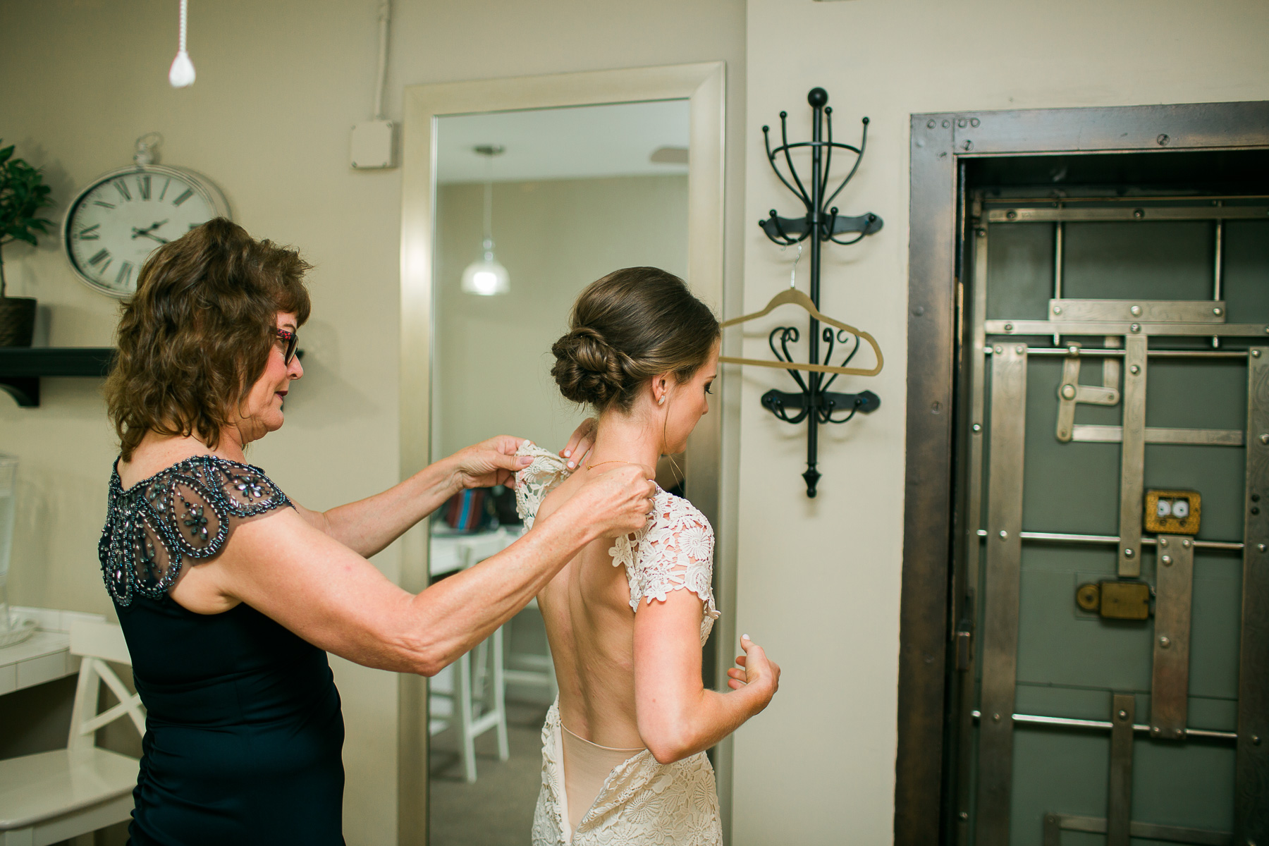 Mom pinning bride's dress