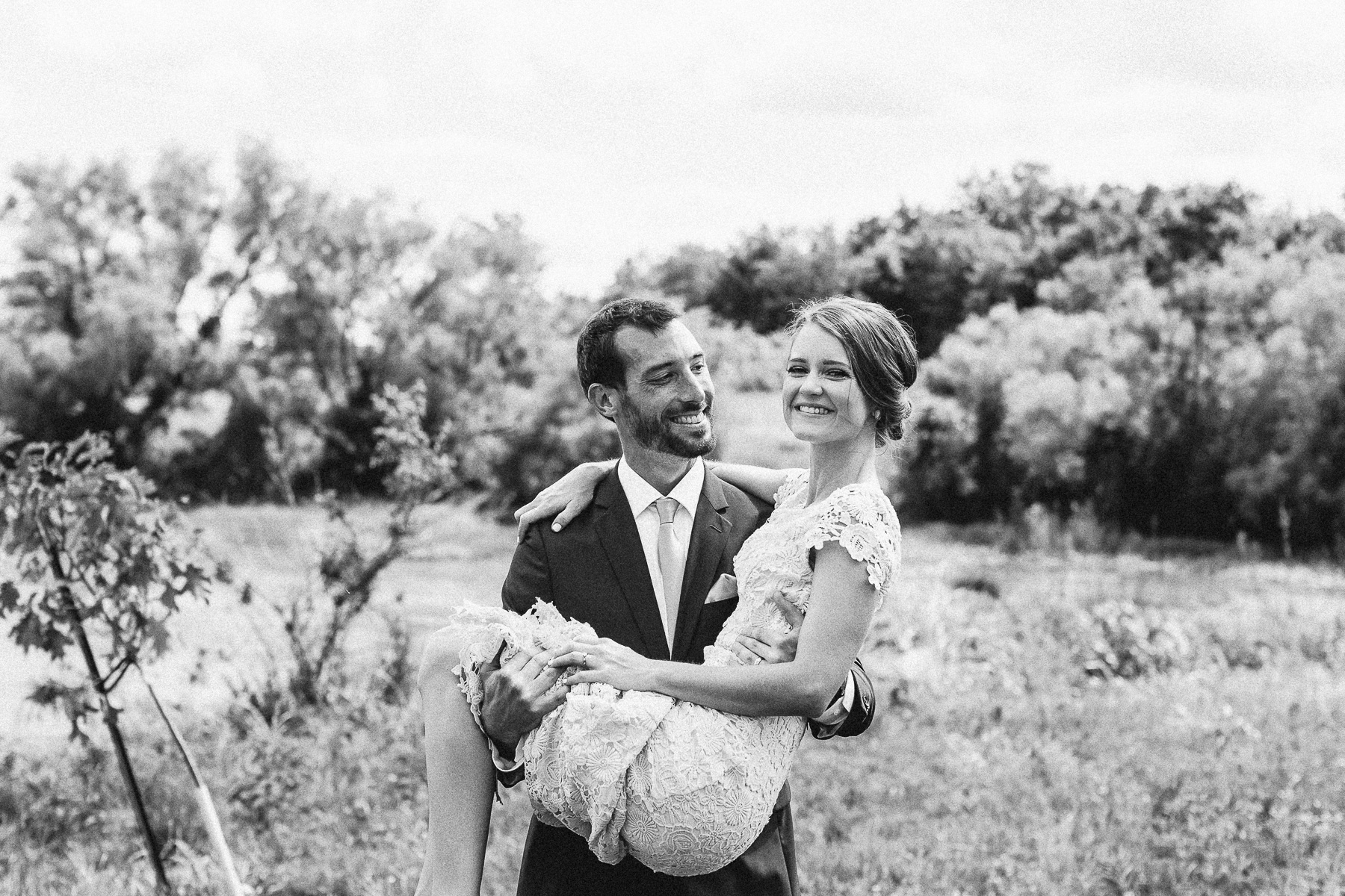 Groom Holding Bride over Grass