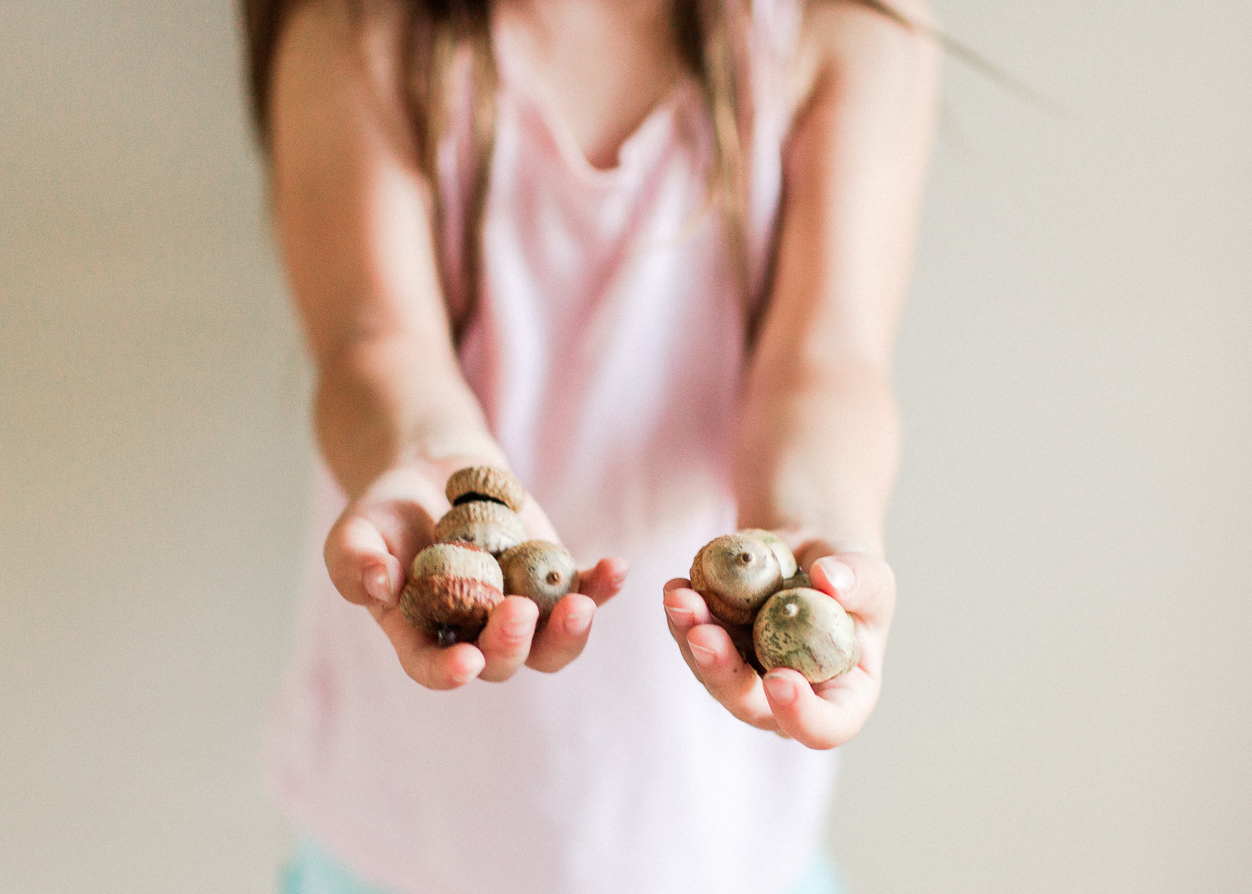 child holding out handfuls of acorns
