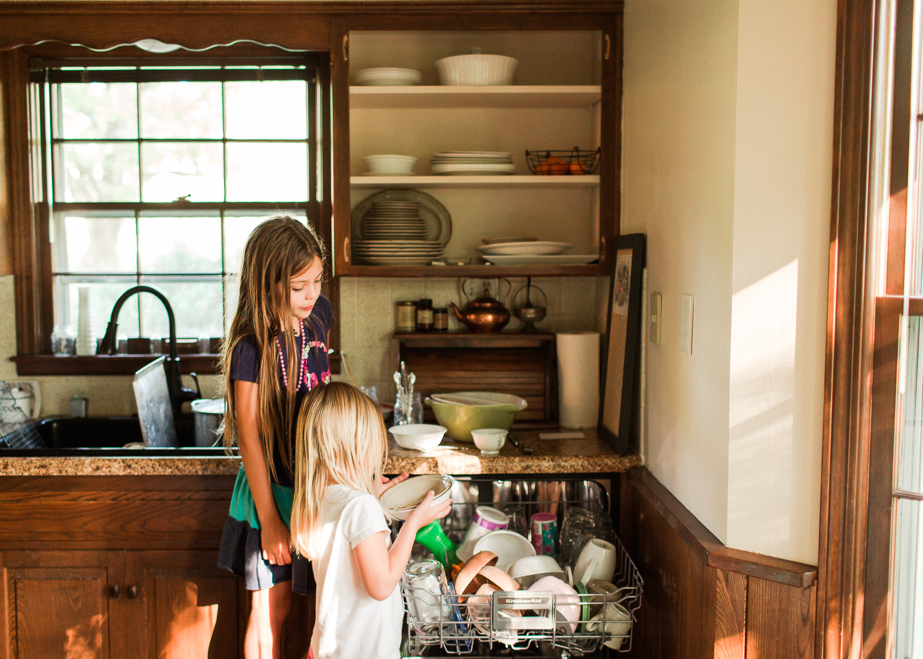 homeschooling girls unloading and loading the dishwasher