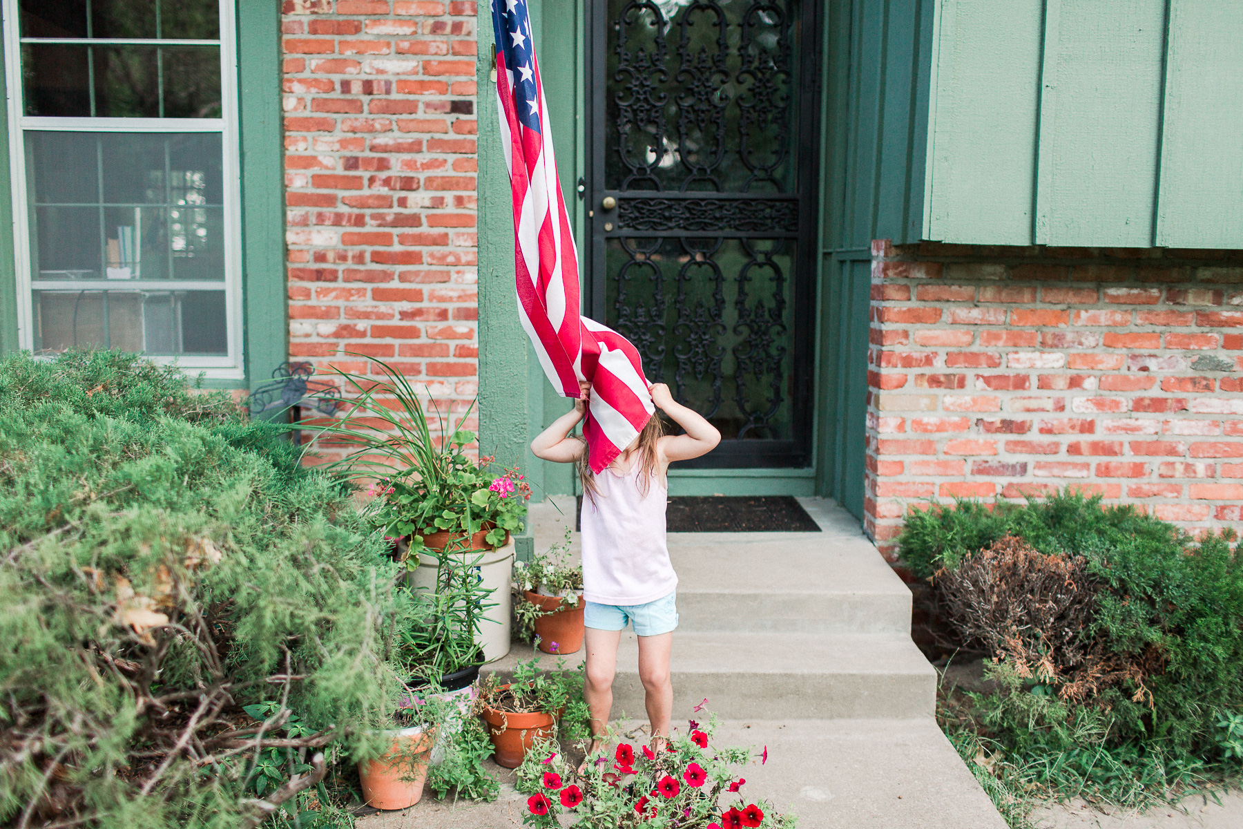 daughter being silly with the American Flag covering her face