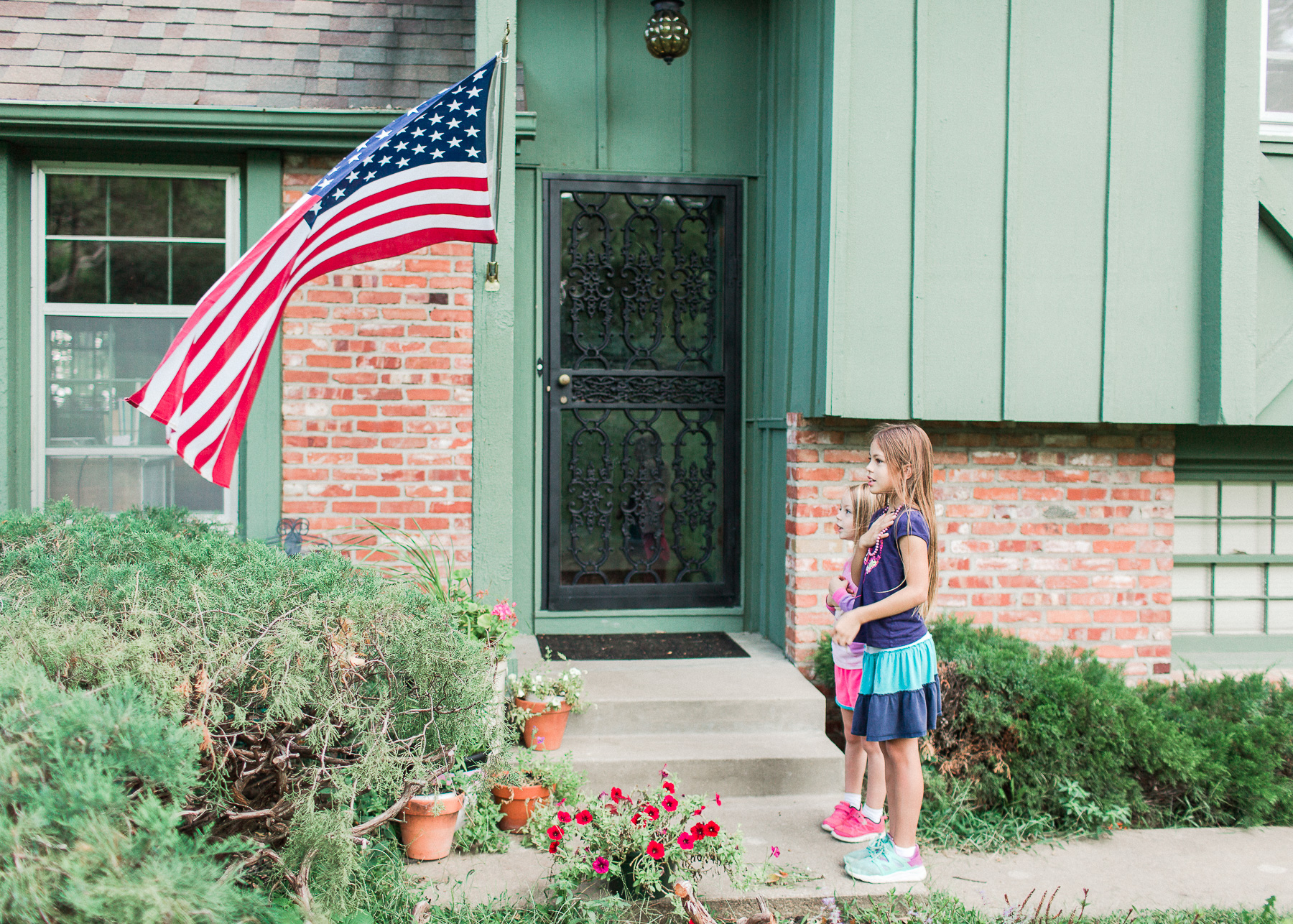 homeschooling girls saluting the American Flag in front of home